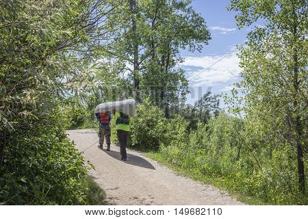 horizontal image of two young men carrying a canoe above their heads down a hiking path  to the lake  surrounded by lush green trees in the summer time.