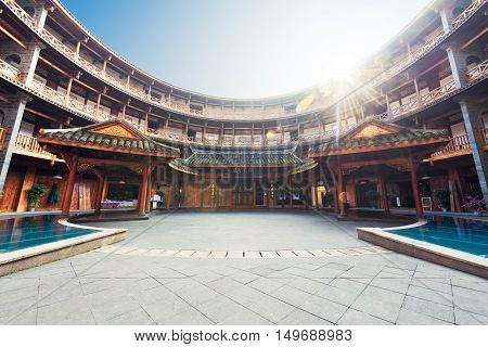 Luodai, Sichuan Province, China - Jan 16, 2016 : Hakka traditional round house with sunrays above the roof.