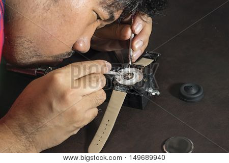 watchmaker try to repair watch with his tools - can use to display or montage on products