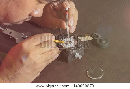watchmaker try to fix a watch on lens fare filter - can use to display or montage on product