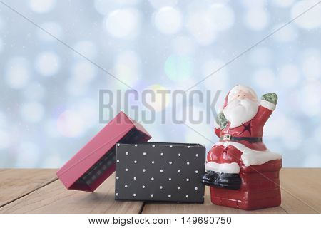 Santa Claus Doll And Open Gift Box On Wood Table On Bokeh And Snow White Drop