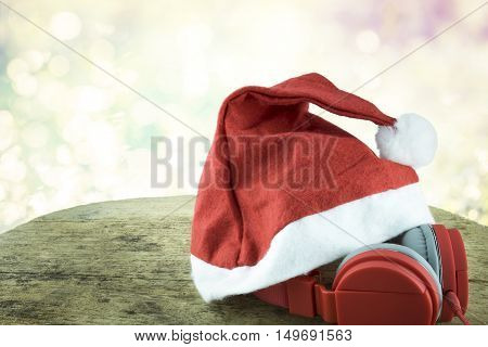Santa Hat And Red Headphone On Woodden Table Over Bokeh Background.