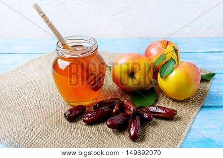 Honey jar dates and apples on burlap napkin. Rosh hashanah concept. Jewesh new year symbols.