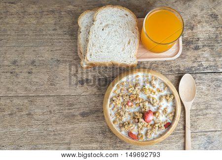 Bowl of breakfast muesli with oat and wheat flakes mixed with dried fruit and nuts in a wooden bowl for a healthy nutritious meal.Served with wholewheat bread and fresh orange juice.