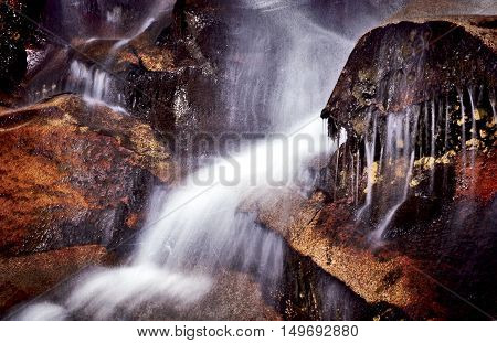 Fast flowing waterfall, blurred motion and strong colours.