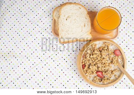 Bowl of breakfast muesli with oat and wheat flakes mixed with dried fruit and nuts in a woodden bowl for a healthy nutritious meal.Served with wholewheat bread and fresh orange juice.