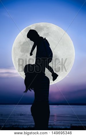 Silhouette of mother and child enjoying with large moon. Mother lifting her little girl up in the air on blue sky background. Friendly family. Cool colors tone. The moon were NOT furnished by NASA.