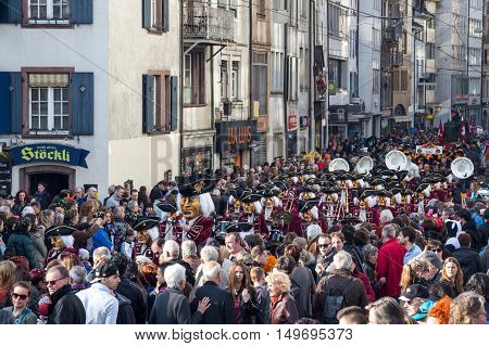 Basel, Switzerland - March 10, 2014: Spectators watching the tradtional carnival parade with dressed up people