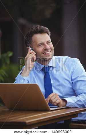 Handsome businessman talking on mobile phone while using laptop at outdoor caf\x96\xA7