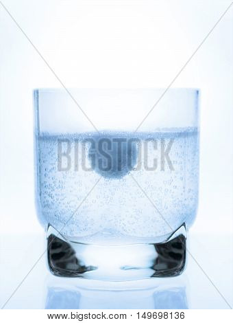 aspirin tablet in a glass of water white background