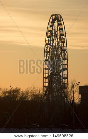 Silhouette of old ferris wheel at sunset in winter