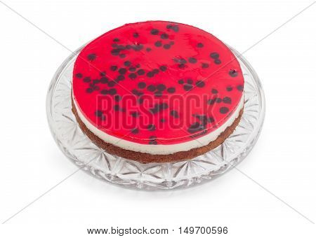 Layered cake with with layers of sponge cake milk jelly and berry jelly on a glass cake serving dish on a light background