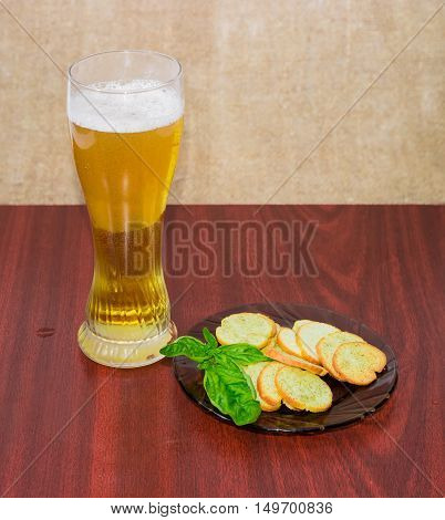 Glass with lager beer rusks with pesto sauce flavor and twig of basil on a saucer on a wooden surface