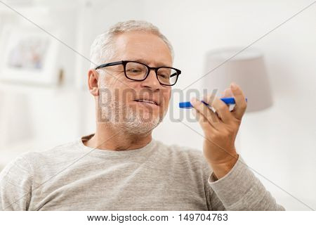 technology, people, lifestyle and communication concept - happy senior man using voice command recorder or calling on smartphone at home