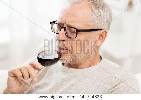 people, alcohol and drinks concept - senior man drinking red wine from glass at home