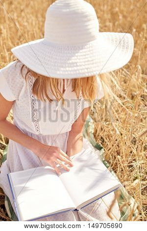 country, summer holidays, literature and people concept - close up of young woman in white straw hat and dress reading book on cereal field