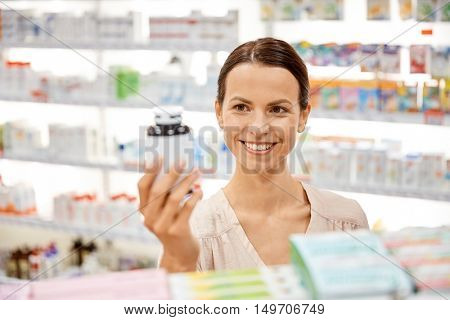 medicine, pharmaceutics, health care and people concept - happy female customer with drug jar at pharmacy
