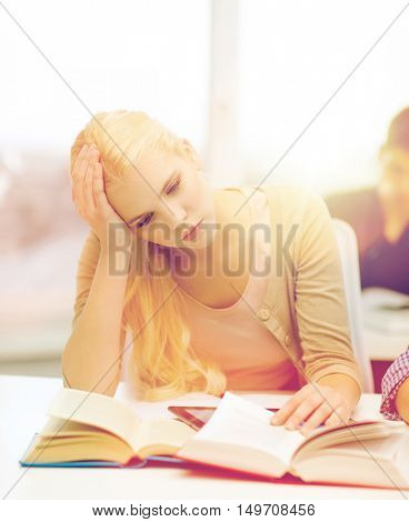 education, technology and internet concept - tired teenage girl student with tablet pc and books preparing for exam