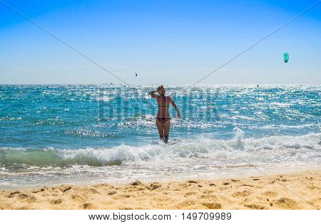 Back view of sexy young lady in bikini wavy sea