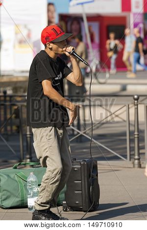 MILAN ITALY - SEPTEMBER 24 2016: A boy beatbox performs in a street of the city center of Milan. The beatboxing is a form of vocal percussion using mouth lips tongue and voice