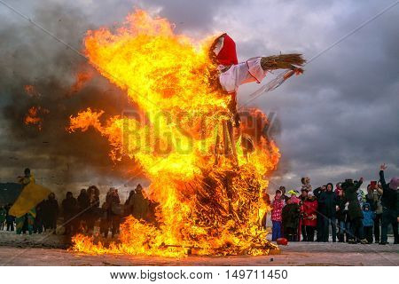 Saint-Petersburg Russia - February 22 2015: Feast Maslenitsa on Vasilyevsky Island. Burning doll - the flames destroyed almost the entire doll. The audience enjoyed the holiday.