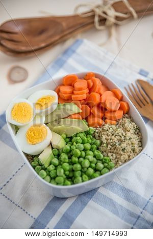 Healthy quinoa bowl with avocado, eggs and vegetables