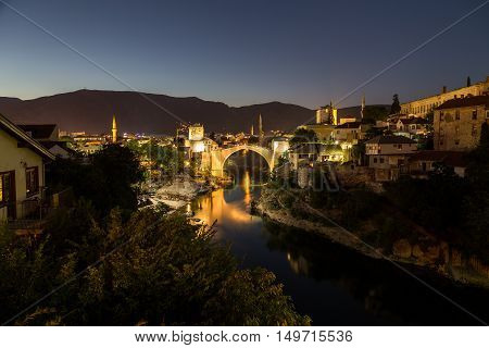 A view of the Mostar skyline at night towards the Old Bridge (Stari Most). Buildings and the River Neretva can be seen.