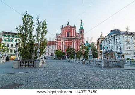 LJUBLJANA SLOVENIA - 27TH MAY 2016: The outside of Franciscan Church of the Annunciation The Triple Bridges and Preseren Square in Ljubljana in the morning