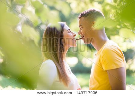 Multi ethnic couple eating together one pice of chocolate outdoor