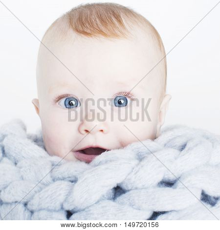little cute red head baby in scarf all over him close up isolated, adorable kid winter clothers smiling, lifestyle real people concept