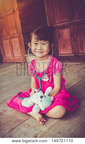 Closeup Adorable Asian Girl Playing Doctor Or Nurse With Plush Toy Bear At Home. Vintage Tone Effect