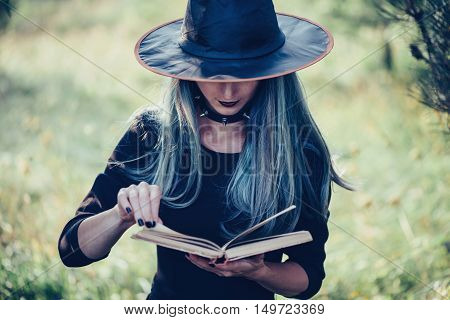 Young woman in costume of witch reading a book of magic outdoor close-up front view. Theme of Halloween and magic