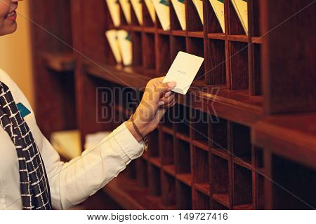Midsection of receptionist with key cards