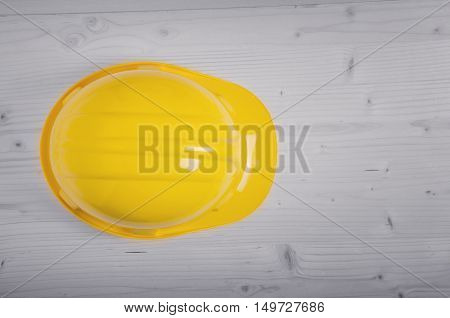 Yellow hard hat (construction helmet) on wooden floor on construction site