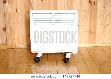 Working white electric convector heater plugged to power line in a wooden house room front view closeup