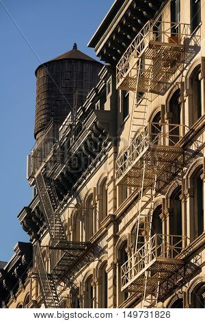 Soho buildings facades with fire escape and wooden water tower. Manhattan, New York City