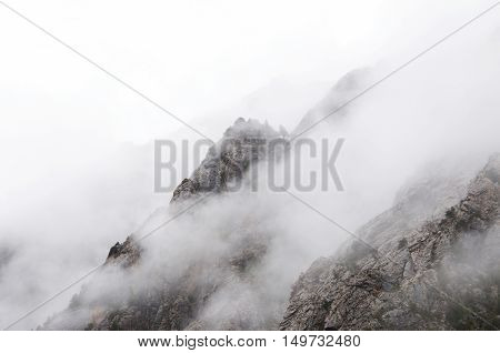 Wet foggy weather in the mountains, the fog slowly descends on the mountain slopes and rocks