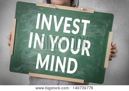 Invest in your mind text written on chalkboard