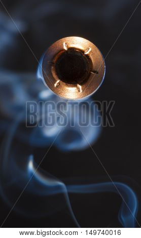 Copper jacketed hollow point direct at the camera with smoke behind