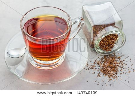 Cup of healthy herbal rooibos red tea in glass cup and dry tea on background