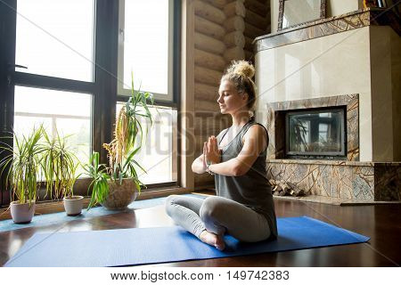 Full length portrait of attractive young woman working out at home, doing yoga exercise on blue mat, sitting in Easy Decent, Pleasant Posture with palms in Namaste, meditating, breathing, relaxing