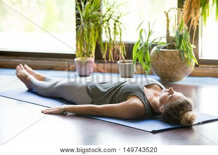 Attractive young woman working out at home, doing yoga exercise on blue mat, lying in Shavasana Corpse or Dead Body Posture , resting after practice, meditating, breathing. Full length