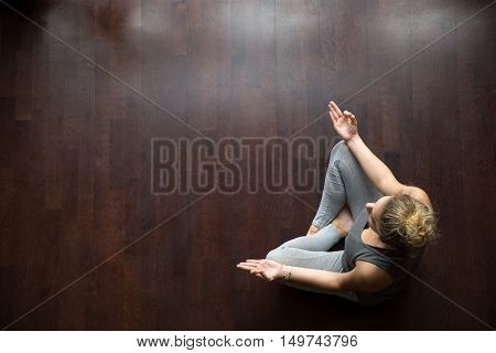 Attractive young woman working out indoors, doing yoga exercise on wooden floor, sitting in Easy Decent, Pleasant Posture , meditating, breathing, relaxing. Full length. Top view. Copy space
