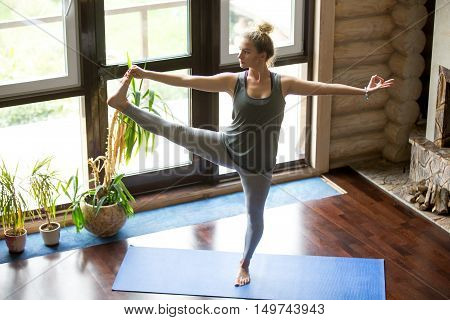 Full length portrait of attractive young woman working out at home in living room, doing yoga or pilates exercise on blue mat, standing in Utthita Hasta Padangustasana, Extended Hand to Big Toe pose