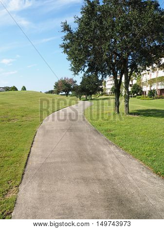 macadam path or walkway by a large grass area and trees