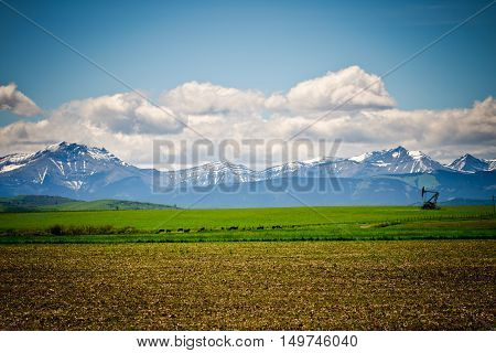Farmland and oil pump in the foothills of Alberta Canada