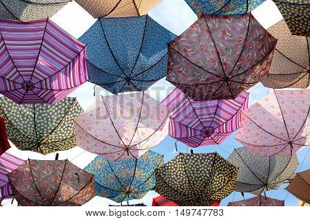 Colorful umbrellas flying in the blue sky