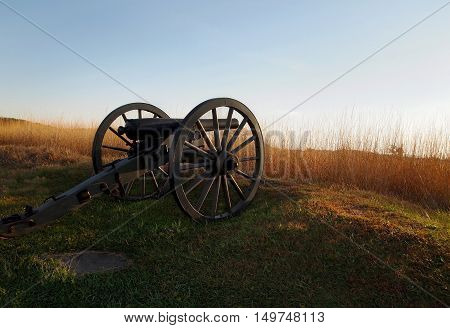 An authentic Civil War cannon sits at the edge of an old battlefield in Gettysburg Pennsylvania on an autumn evening at sunset.