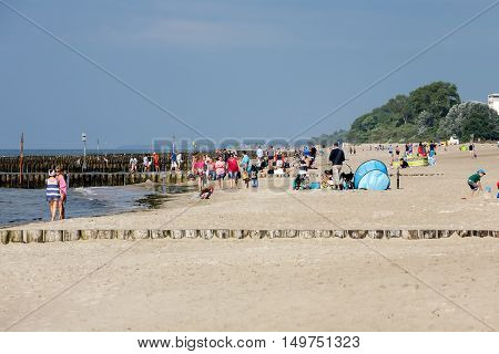 KOLOBRZEG POLAND - JUNE 29 2016: Unidentified vacationers enjoying the sunshine on the sandy beach of the Baltic Sea