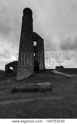 A chimney and some derelict buildings at a disused mine Magpie Mine in the Peak District